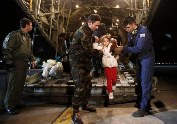 A man (C) and his daughter (2nd L), both rescued from the Norman Atlantic ferry, disembark from a Greek Airforce C-130 military cargo aircraft at the Elefsina military airport near Athens December 29, 2014. Rescue teams evacuated more than 400 people from a car ferry that caught fire off Greece's Adriatic coast in a 36-hour operation on roiling seas, but 10 people were killed in the disaster. Italian and Greek authorities continued an air search of the sea around the vessel while they sought to verify the number of passengers who had been on board, fearing that many people could be missing. The fire broke out on Sunday on a vehicle deck of the Norman Atlantic ferry, whose manifest said should be carrying 478 passengers and crew and more than 200 vehicles. Rescue efforts were complicated by bad weather.  REUTERS/Yannis Kolesidis/Pool   (GREECE - Tags: DISASTER MARITIME TRANSPORT TPX IMAGES OF THE DAY)
