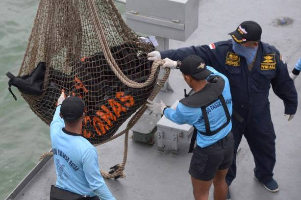 Bags containing dead bodies of the passengers of AirAsia Flight 8501 are lifted onto Indonesian navy vessel KRI Banda Aceh at sea off the coast of Pangkalan Bun, Indonesia, Saturday, Jan. 3, 2015. Indonesian officials were hopeful Saturday they were honing in on the wreckage of the flight after sonar equipment detected two large objects on the ocean floor, a full week after the plane went down in stormy weather. (AP Photo/Adek Berry, Pool)