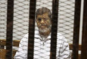 FILE - In this May 8, 2014 file photo, Egypt's ousted Islamist President Mohammed Morsi sits in a defendant cage in the Police Academy courthouse in Cairo, Egypt. An Egyptian court sentenced former President Mohammed Morsi to death, Saturday, May 16, 2015,   for passing state secrets. (AP Photo/Tarek el-Gabbas, File)